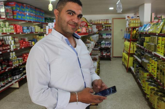 Omar, a shop owner, makes his store more attractive with Dalili
